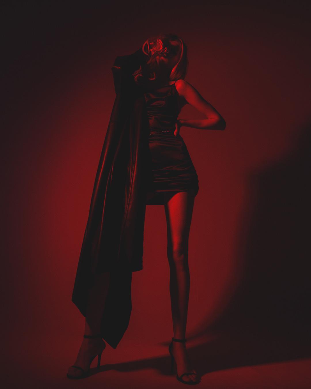 eine schwarz gekleidete frau getaucht in schwaches rotes licht
